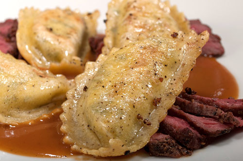 Pan Seared Pepper Dough Mezzaluna with Sliced New York Strip Steak and Demi Glace