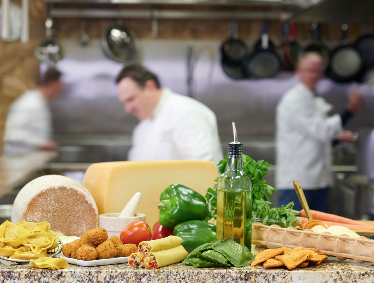 A display of pasta and ingredients with chefs working in the background